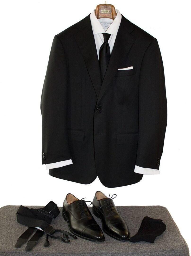 Esimerkki etiketinmukaisesta hautajaisasusta; tumma puku, valkoinen kauluspaita, musta silkkisolmio, valkoinen pellavataskuliina hillitysti taiteltuna, mustat sukat, mustat nahkaiset nauhakengät sekä mustat olkaimet.