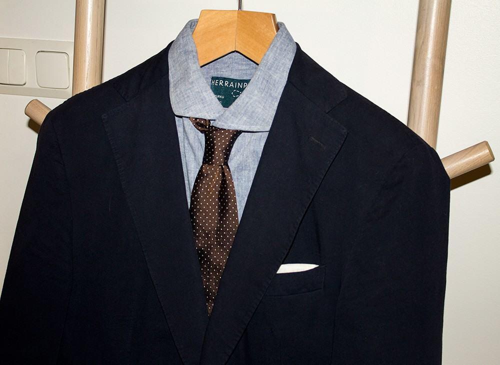 Tummansininen irtotakki, vaaleansininen paita, ruskea solmio ja valkoinen taskuliina on pomminvarma yhdistelmä.