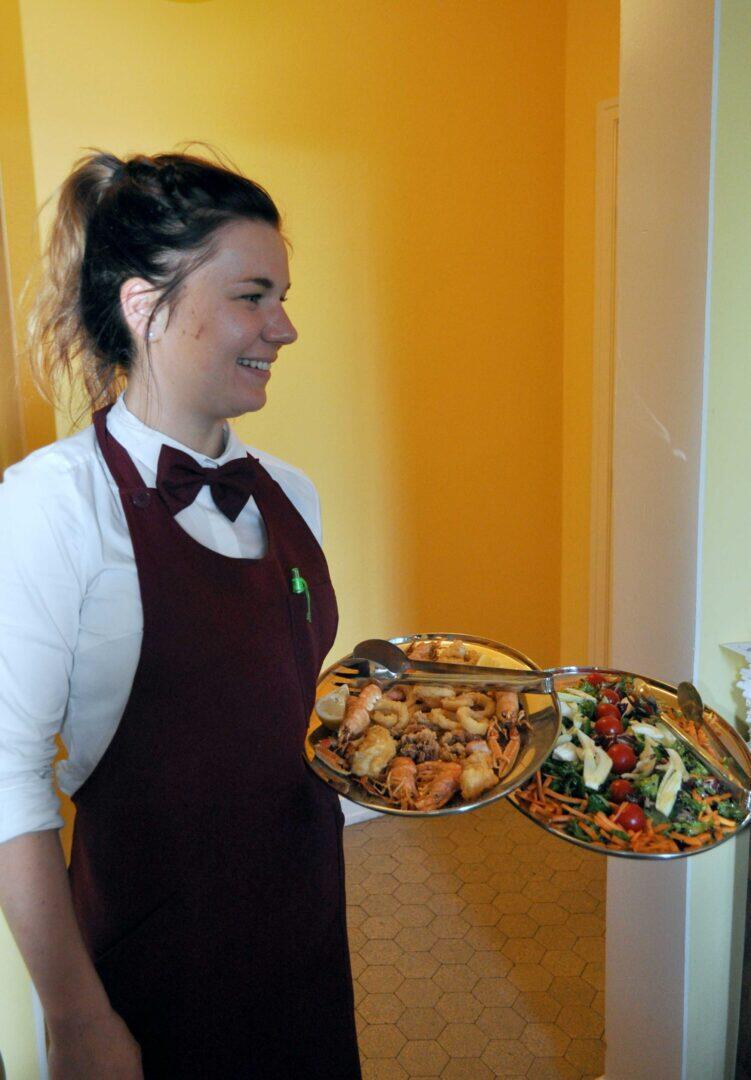 Salihenkilökunta huolehtii ruokailijoista hymy huulillaan.