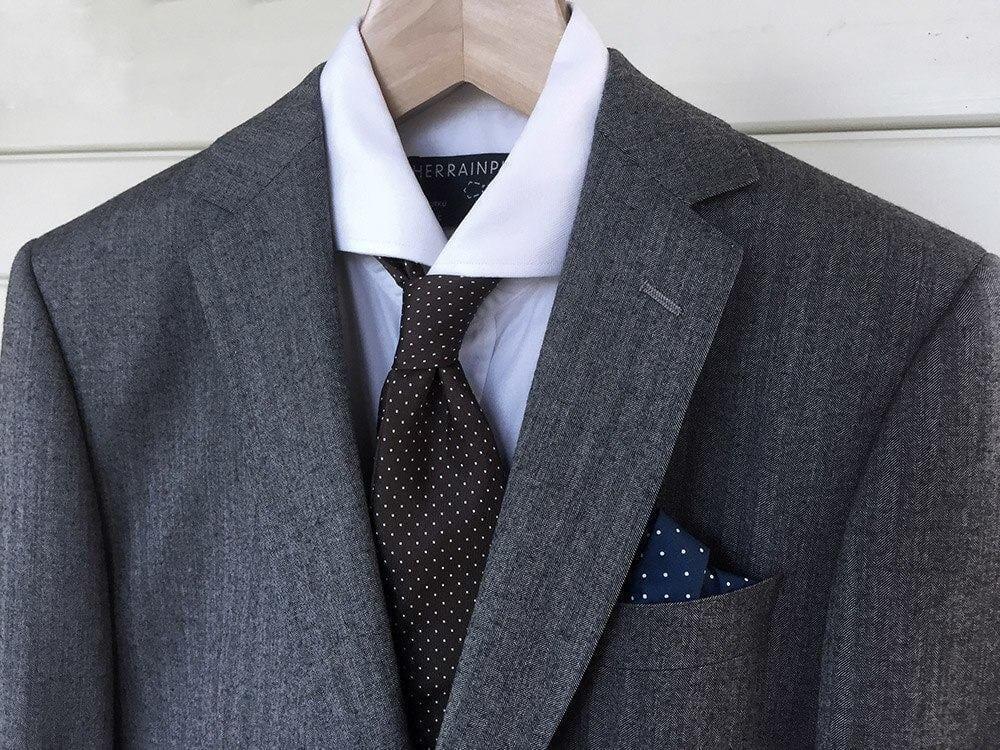 Hillitty keskiharmaa villakangaspuku valkoisella kauluspaidalla, hillityllä solmiolla ja taskuliinalla on oivallinen valinta cocktailasuksi.