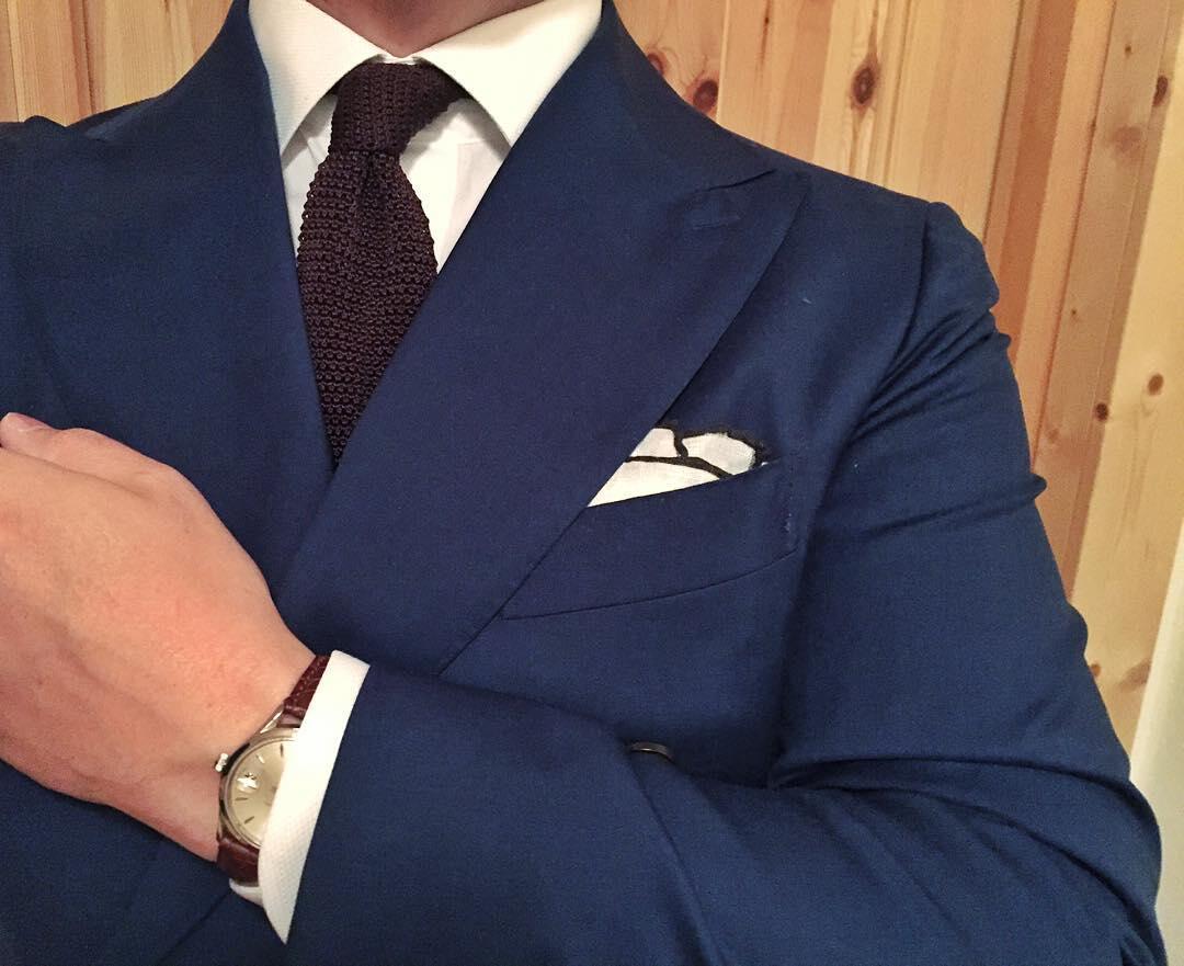 Sininen puku, valkoinen kauluspaita, ruskea neulesolmio ja valkoinen pellavaliina.