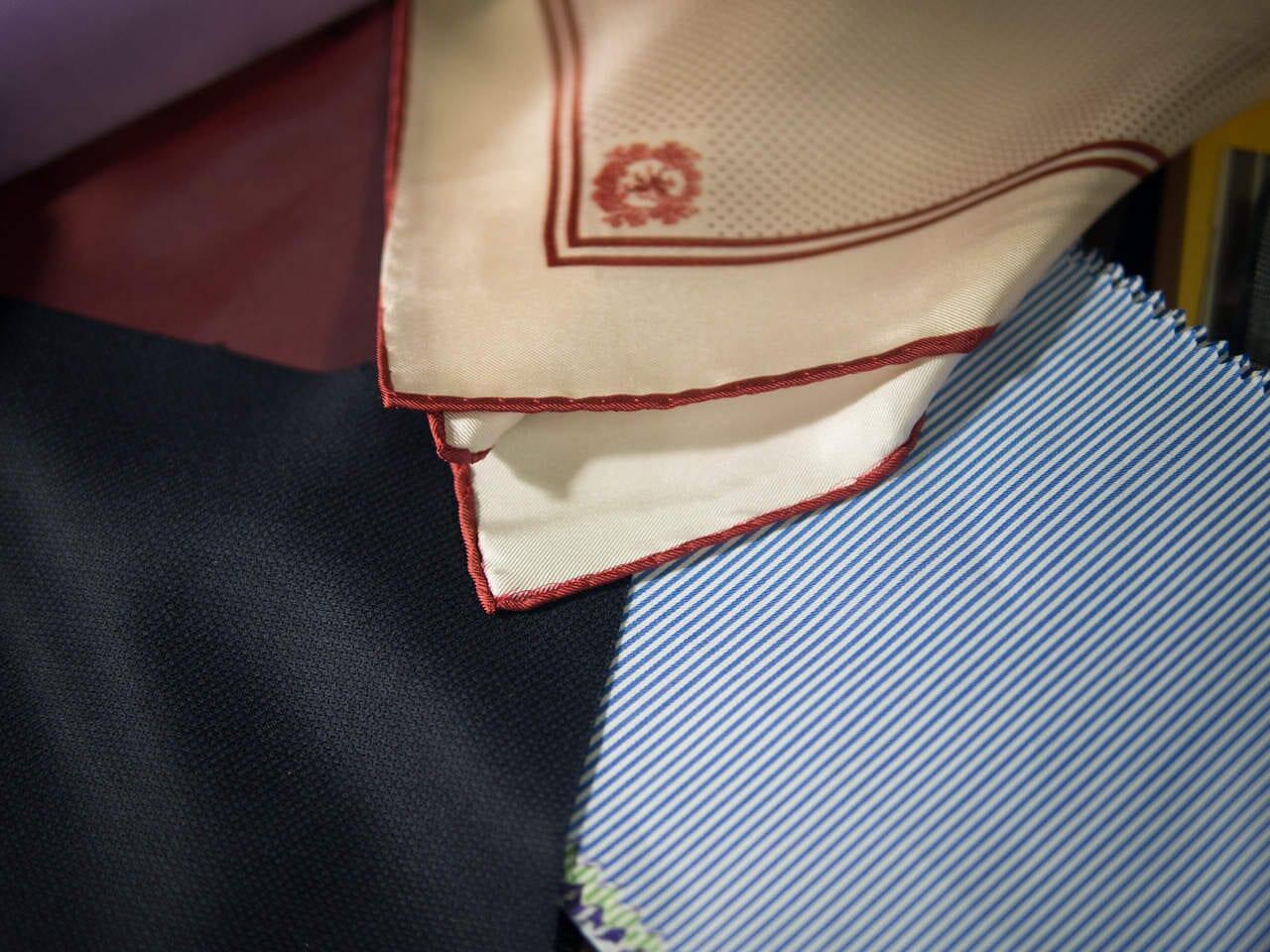 Lopulliset kangasvaihtoehdot; tummansininen kangas, viininpunainen vuorikangas, käsinrullattu Signh&Magnus-taskuliina sekä paitakangas.