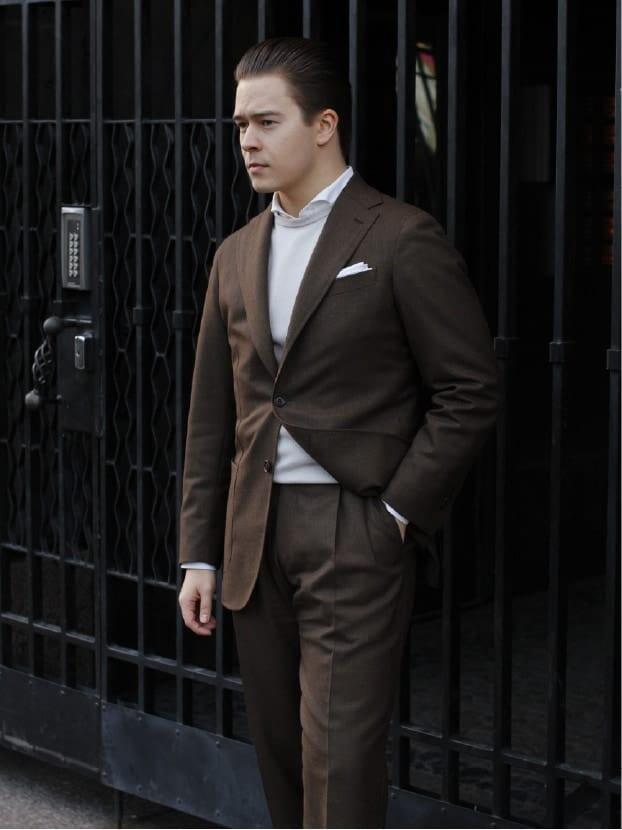 Ruskea puku paikkataskuilla, valkoisella kauluspaidalla ja valkoisella pellavataskuliinalla on täydellinen kombinaatio. Kuva: Herrainpukimo
