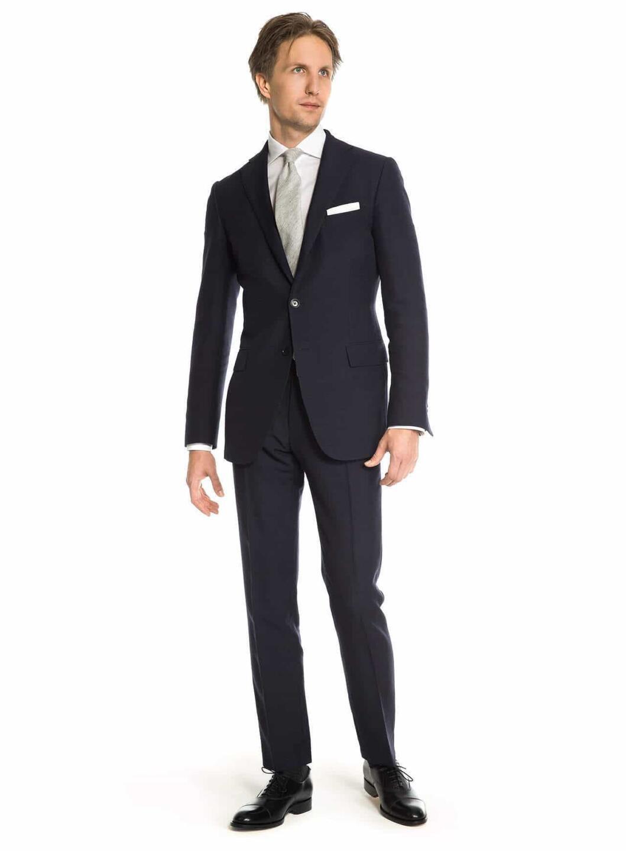 Tummansinisen puvun ympärille voi rakentaa lähes minkälaisen ja -tasoisen asukokonaisuuden. Kuva: Herrainpukimo
