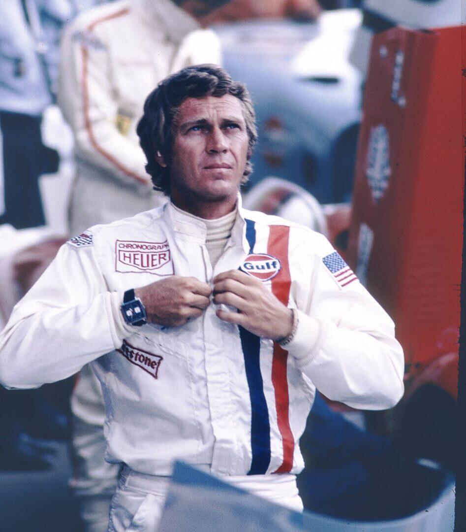 Steve McQueen Monaco ranteessa Le Mans -elokuvassa. Kuvassa näkyvän ajopuvun McQueen lainasi hyvältä ystävältään, kilpa-ajaja Jo Siffertiltä, joka oli elokuvan teon aikaan Heuerin ja Gulfin brändilähettiläs - jonka on osaltaan sanottu vaikuttaneen Monacon, Gulfin ja Heuerin väliseen yhteistyöhön. Kuva: TAG Heuer