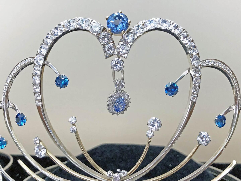 Miss Suomi -voittaja saa muistoksi omasta vuodestaan uniikin, vuosittain vaihtuvan korun, joka roikkuu kruunun keskellä.