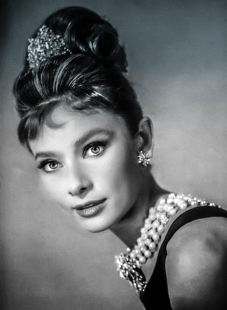 Audrey Hepburn elokuvassa Aamiainen Tiffanylla (v. 1961). Kuvassa näkyvät korut ovat Tiffanyn ja musta hihaton puku on Givenchyn käsialaa, joka on niin ikään LVMH:n omistuksessa.