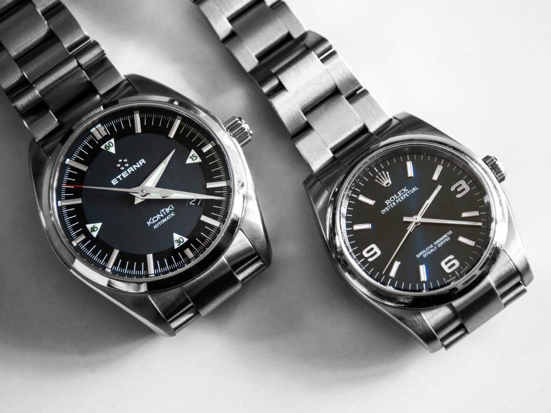 Mustasävyinen kellokokoelma muodostuu kahdesta teräsrannekkeisesta kellosta.